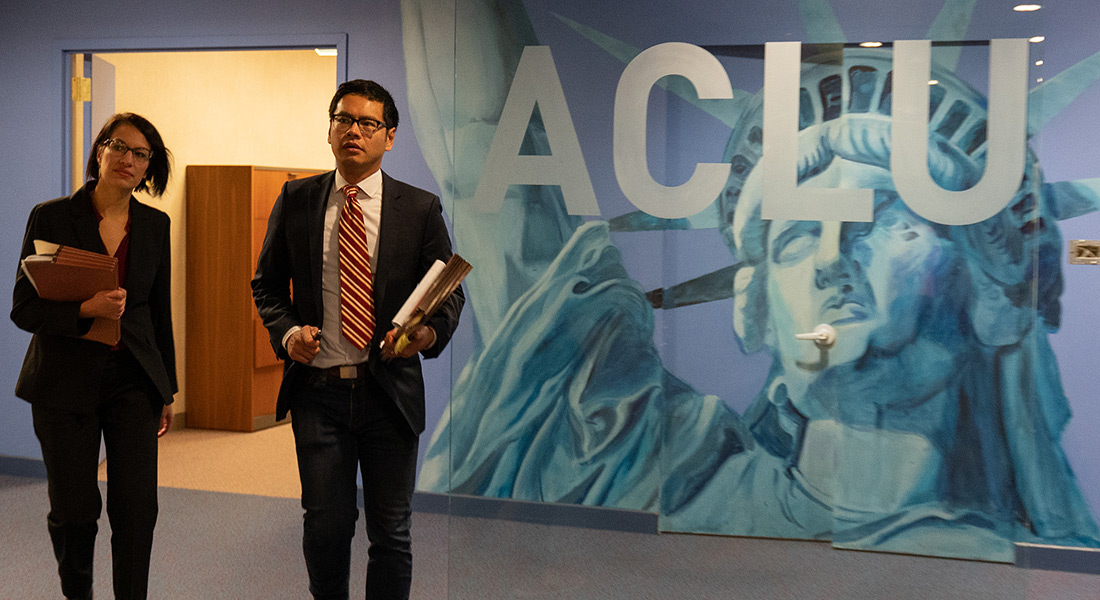 ACLU lawyers Brigitte Amiri and Dale Ho stand in front of an ACLU mural featuring the Statue of Liberty