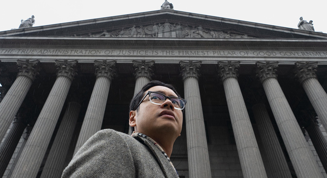 Looking up at ACLU lawyer Dale Ho standing in front of a courthouse with classical architecture