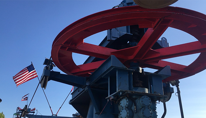 A large red machine is framed against a clear blue sky.