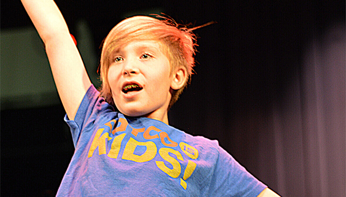 A CATCO youth performer onstage with his right arm raised
