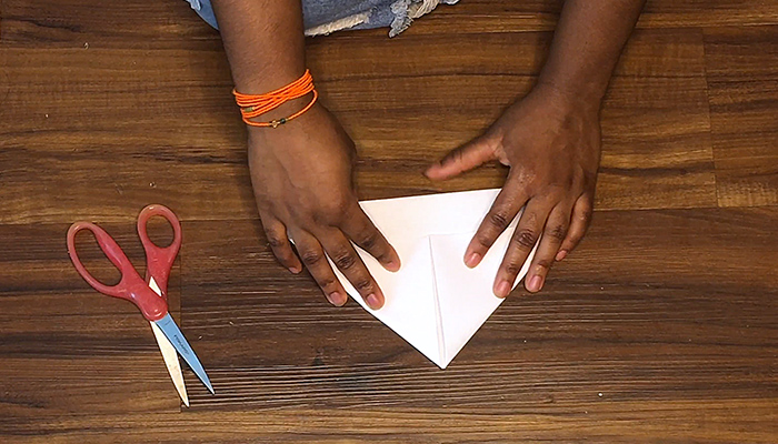 The hands of Claudia Owusu making a paper boat