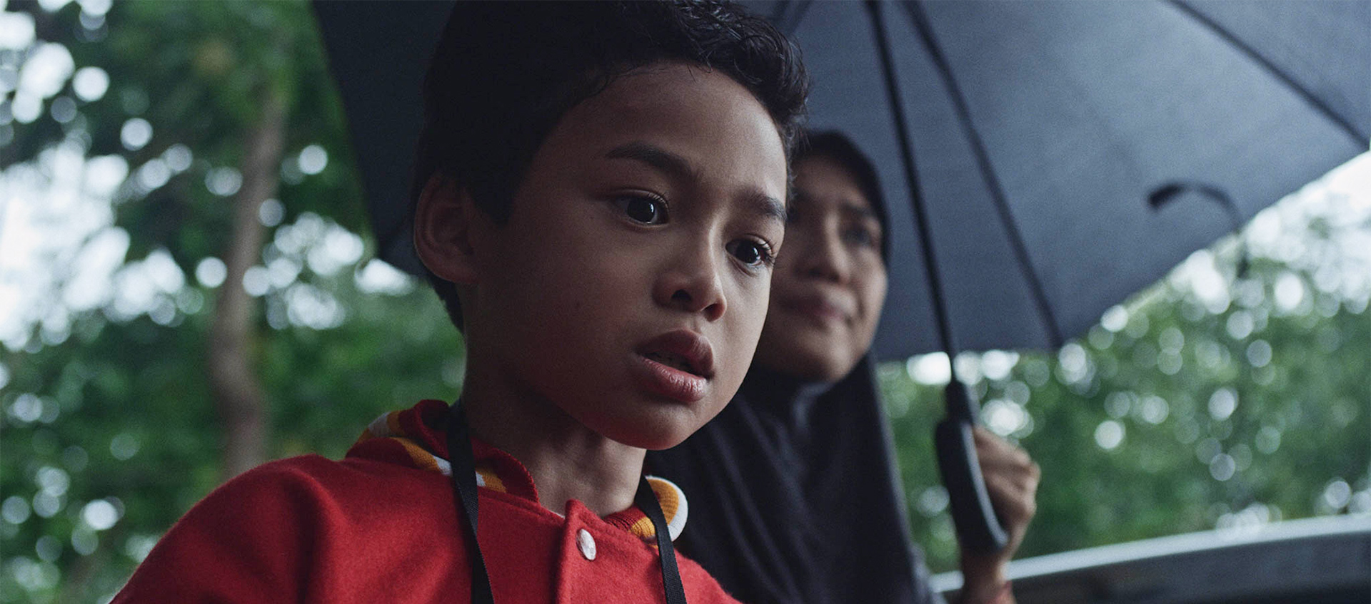 A young child stands under an umbrella