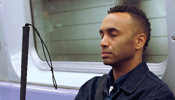 Filmmaker Rodney Evans seen shoulders up, sitting on a subway train with eyes closed, holding his cane, in a scene from his documentary Vision Portraits