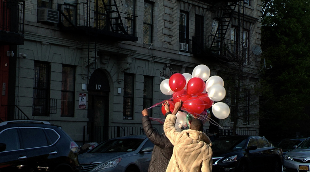 Two people walk down a city street carrying red and white balloons.