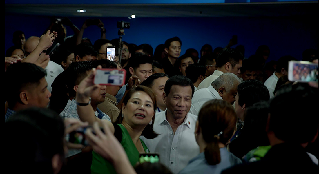 President Duterte smiles while surrounded by a crowd and cameras