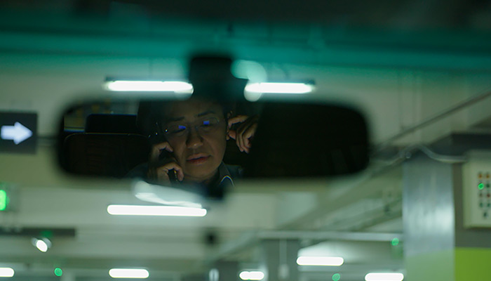 Journalist Maria Ressa, talking on a cell phone, is seen reflected in a car's rear view mirror