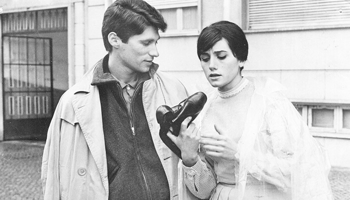 A black-and-white still of the film's young couple Julio and Ilda, with the latter examining a pair of shoes