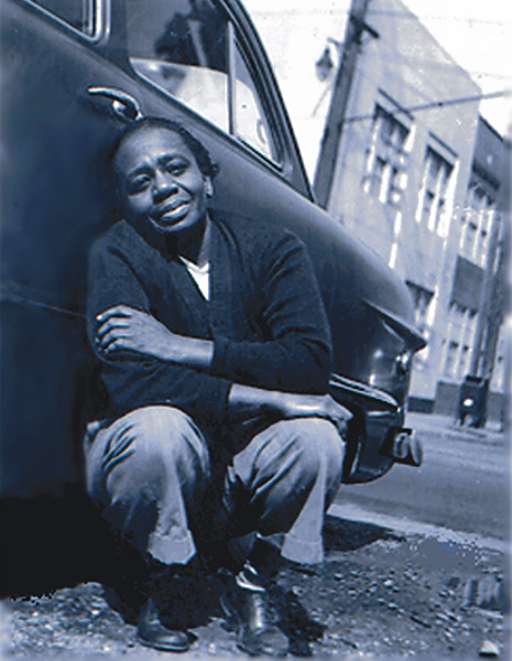 Ruth Ellis crouches down against a car with her arms drawn around herself.