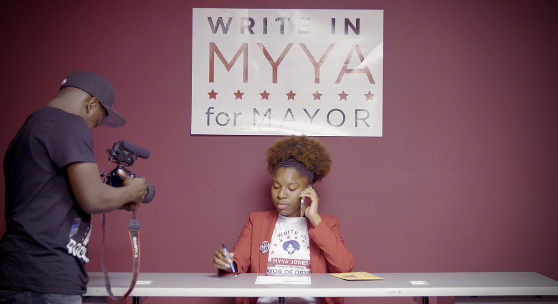 A cameraperson films mayoral candidate Myya Jones while she talks on a phone in front of a campaign sign