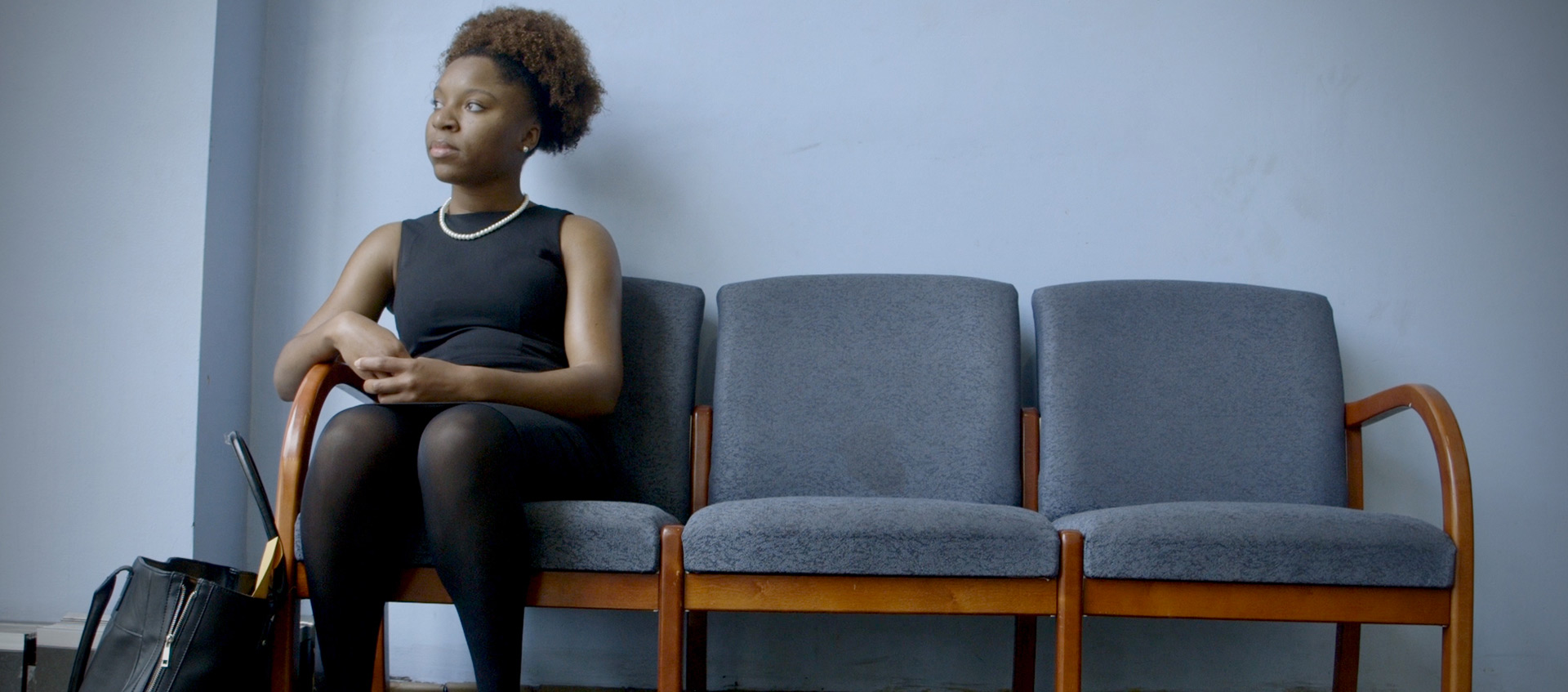 Mayoral candidate Myya Jones sits on a bench in a waiting room