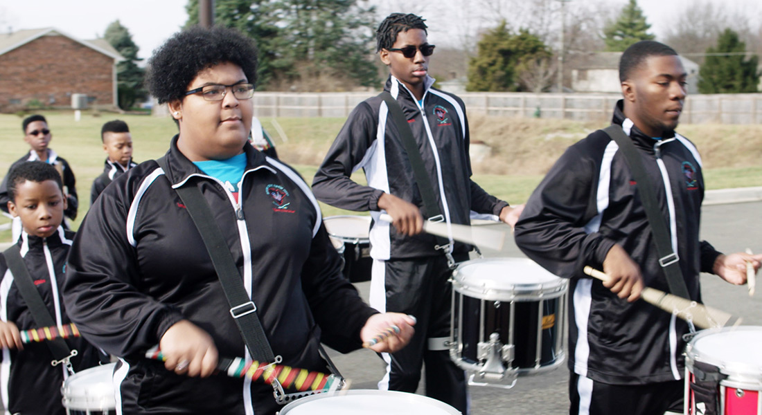 Several young men and boys in black track suits play marching snare drums