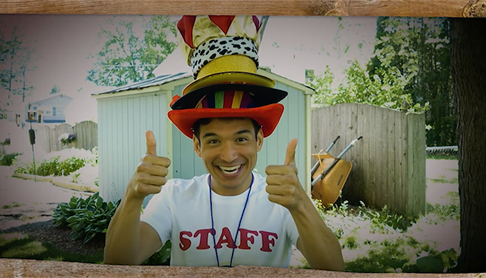 Actor Zachary Noah Piser smiles and wears a pile of hats and gives two thumbs up during an episode of PBS Thirteen's Camp TV