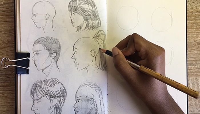 The hand of Columbus artist Joy Annorzie draws a person's profile in her sketch book