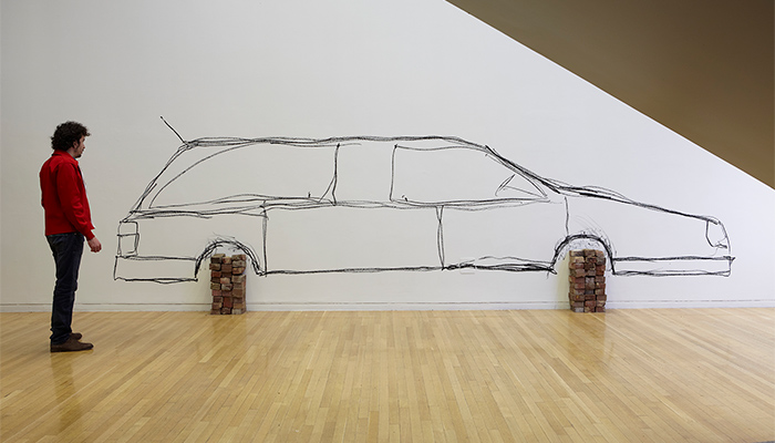 A car is drawn on a wall in hasty, scrawling black marks. The wheels of the car are physical stacks of bricks.
