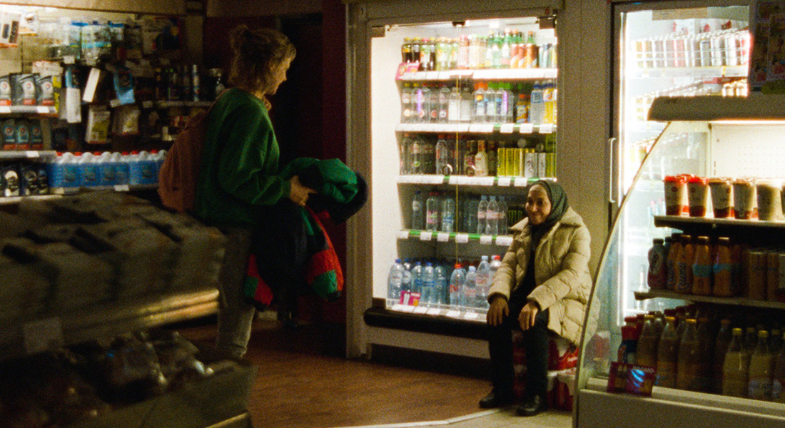 Khadija sits in a convenience store talking with teenage girl
