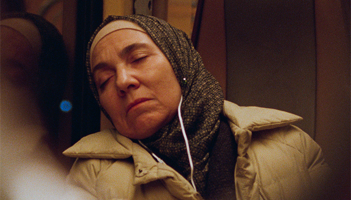 Khadija sleeps on the train with headphones on
