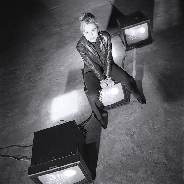The artist Gretchen Bender sits on top of a television.