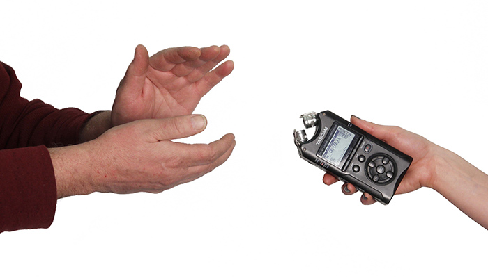 A person out of frame except for their hands claps on the left side while on the right, a hand with a small recorder in it extends toward the person clapping