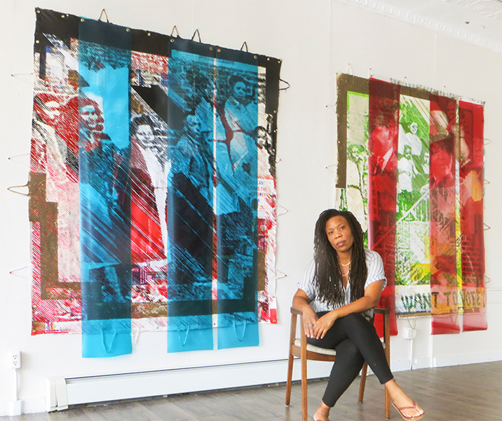 Artist Tomashi Jackson is seated in front of two of her collage paintings