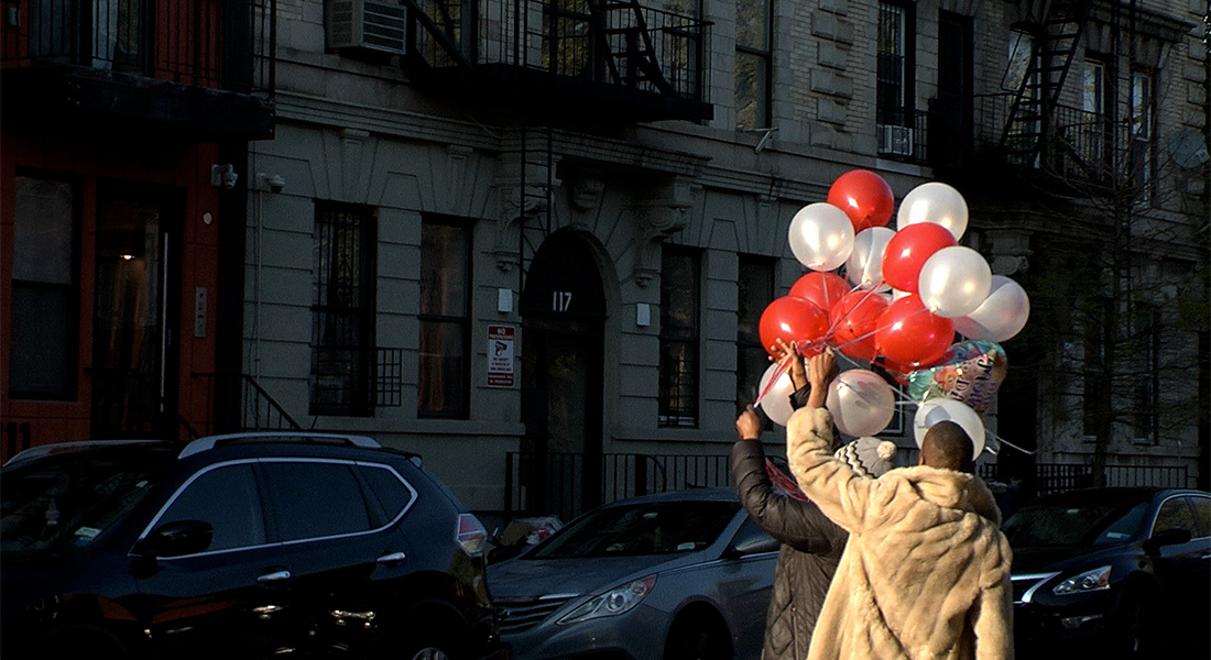Two men hold up bunches of red and white balloons outside an old residential building in Brooklyn