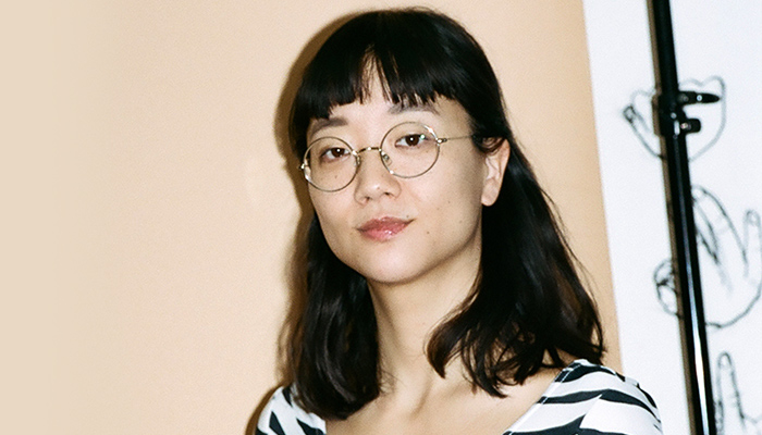 Photo of Christine Sun Kim in front of beige wall. Christine is wearing glasses and striped shirt