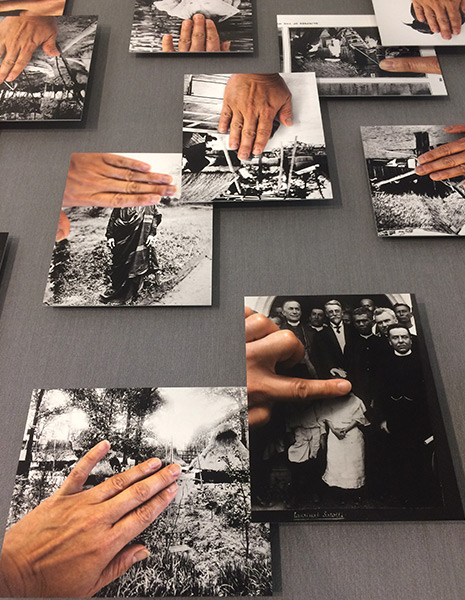 A selection of photos on a table. Hands and finger covers portions of the image on each