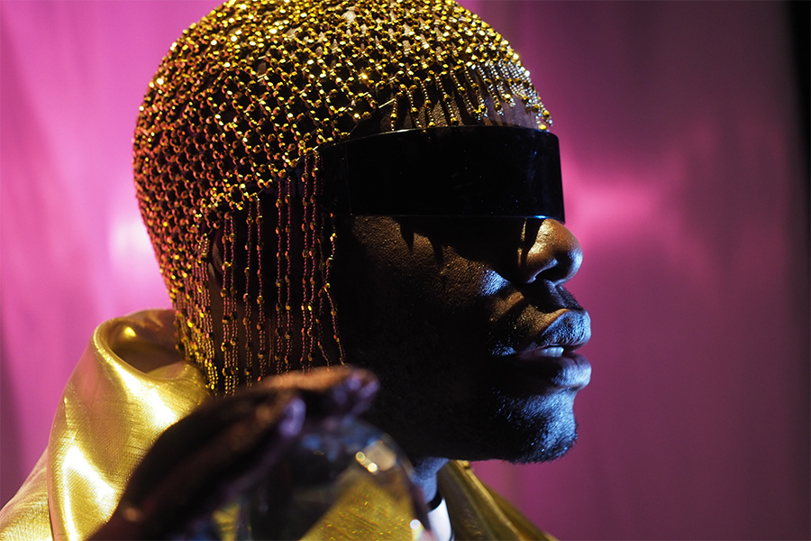 Artist Jaamil Olawale Kosoko wears gold clothes and headdress and black sunglasses while standing against a shimmering purple background.
