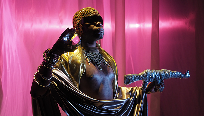 Artist Jaamil Olawale Kosoko, dressed in gold clothes and headdress, stands against a shimmering purple background while holding a crystal orb in one hand and a gun wrapped in sequined fabric.