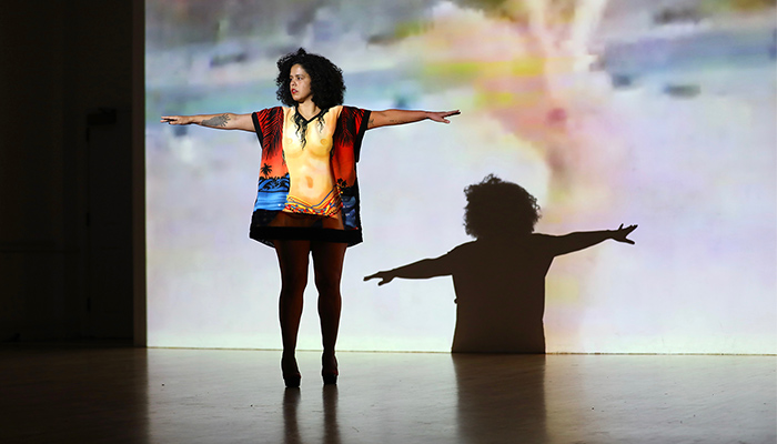 Awilda Rodríguez Lora  stands on a stage with arms outstretched wearing a shirt with a nude female torso