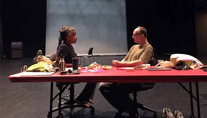 Bebe Miller (on left) and Paul Lazar (on right) seated and facing each other at a red table