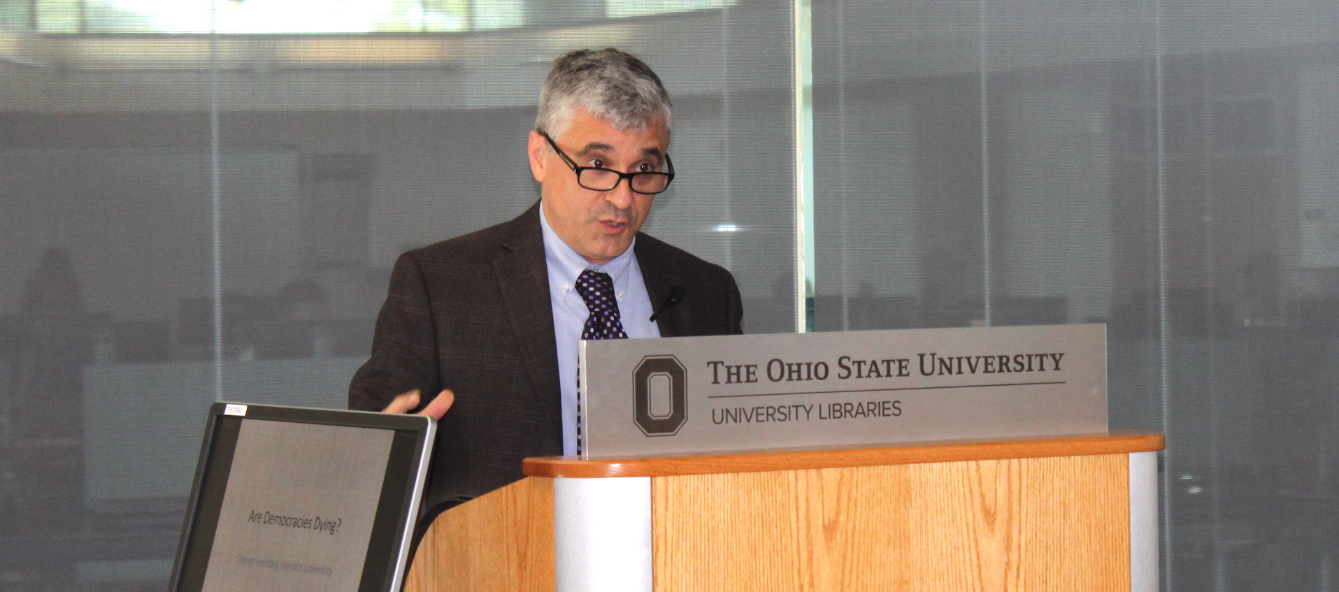 A white man with salt and pepper hair and black rimmed glasses speaks at a wooden podium topped by a gray sign with Ohio State University branding