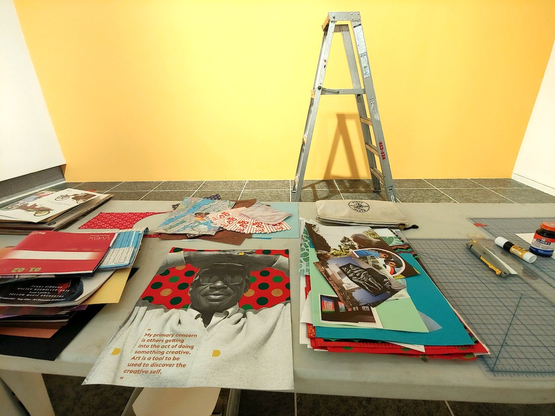 A collection of potential collage materials on a table in the foreground, with a yellow wall with a ladder in front of it in the background