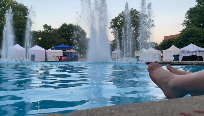 The surface of a pool with fountains in the backdrop and two bare feet stretched out poolside in the foreground