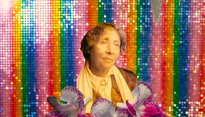 A vintage sepia image of a woman holding white and violet orchids against a sequined rainbow background