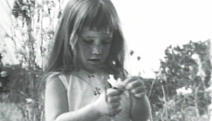 black and white image of a little girl picking the petals off a daisy, from a historic Lyndon Johnson campaign ad