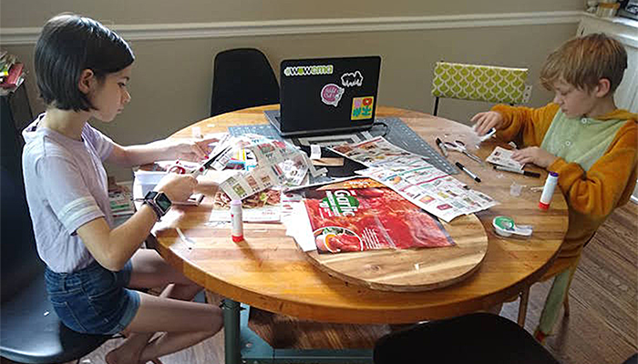 A young girl and boy sit and work at a table covered in printed circulars, flattened packaging, and art supplies