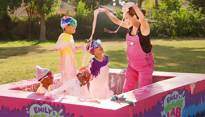 A woman in pink overalls plays with four children in a small outdoor pool filled with pink slime