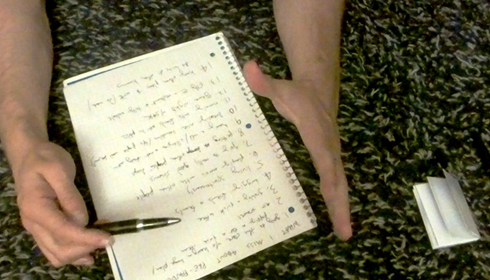 The hands of artist Noah Demland as he holds a pen and goes over a list of 'zine ideas written in a notebook
