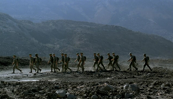 A group of soldiers march on a hillside