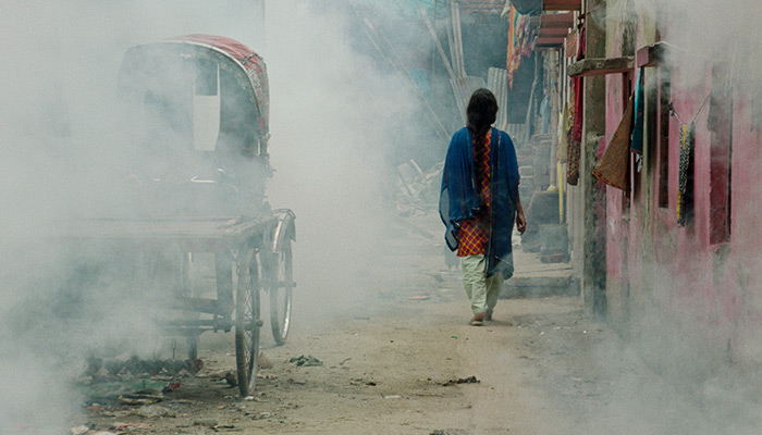 A woman walks away from the camera down a smoky street