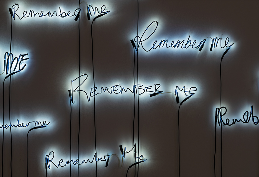 "The words ""Remember Me"" are sculpted in neon and lit against a white wall."