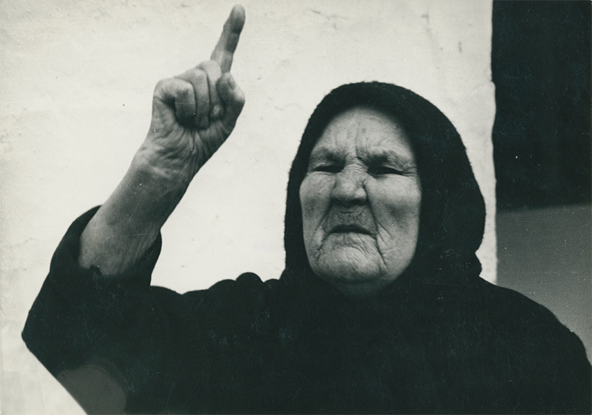 A black and white still of an elderly woman with her index finger raised in toward the sky