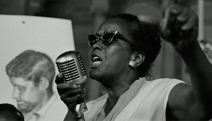 Image of Ella Baker wearing sunglasses and standing at a microphone speaking passionately
