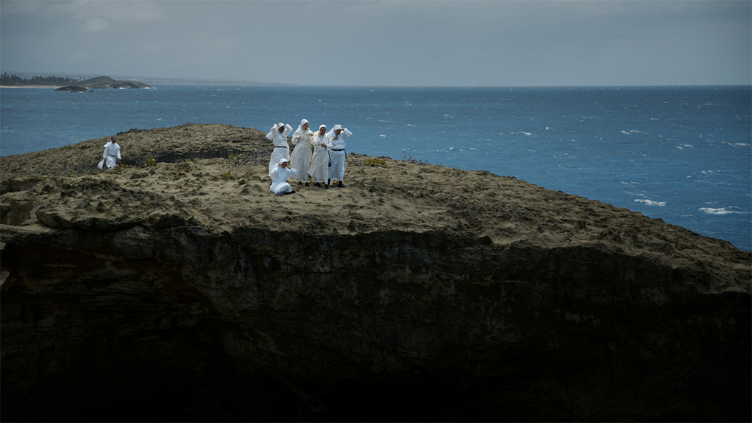 A group of people wearing white robes and head coverings stand near an edge of a cliff by a sea