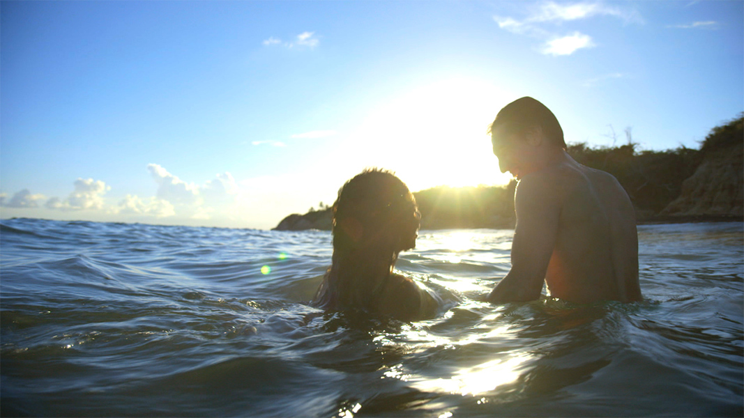 Two people laugh and swim in the sea.