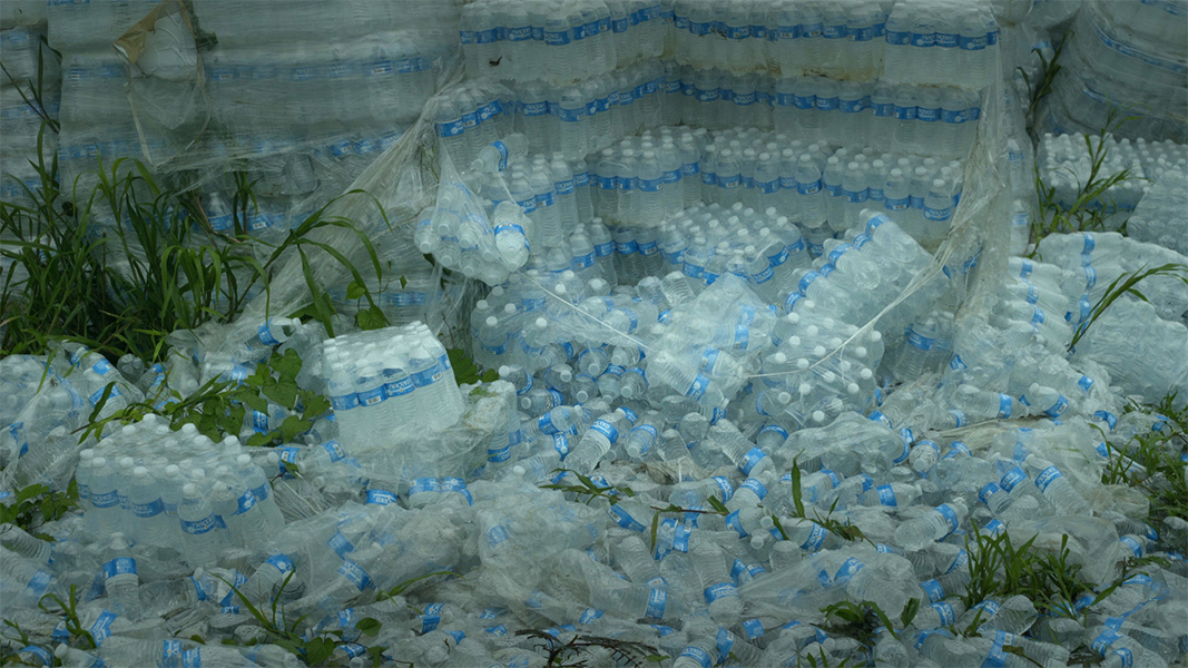 Hundreds of cases of water bottles are strewn on the ground and stacked in rows.