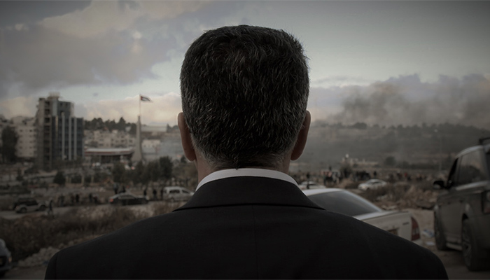 A man in a suit, seen from behind and from the shoulders up, looks out over a hazy city landscape.