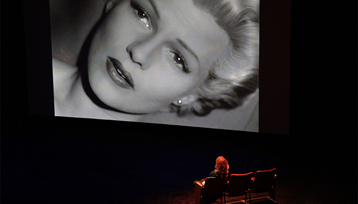 Nina Menkes sits on stage and watches a black and white film scene that depicts a woman's face up close.