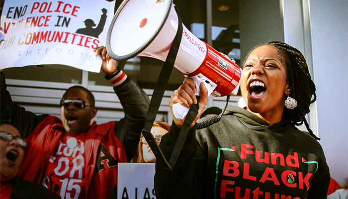 A woman shouts passionately into a megaphone while a man behind her holds up a sign supporting the end of police violence.