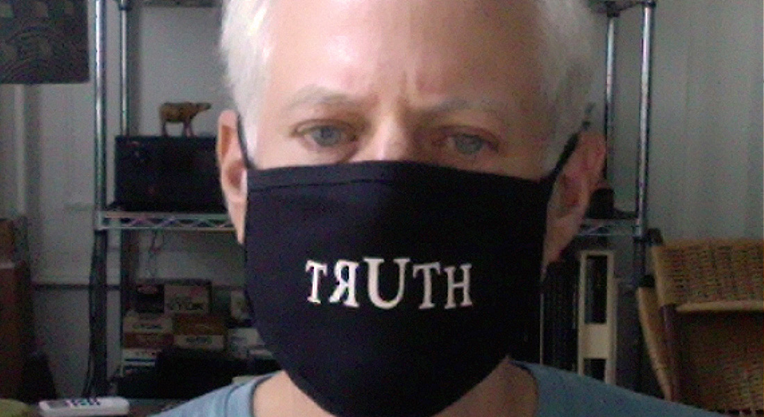"Marshall Reese wearing a facial covering that reads ""truth"""